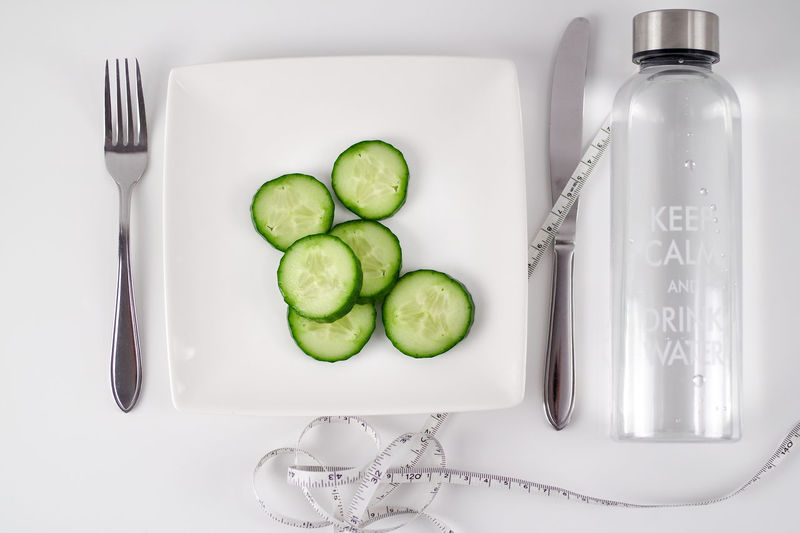Cucumber Eating Forklift Goals Green January Measuring Tape New Years Resolution  Close-up Copyspace Cucumber Slices Day Dietfood Dieting Drink Water Freshness Indoors  Loosing Weight  Measurement No People White Background