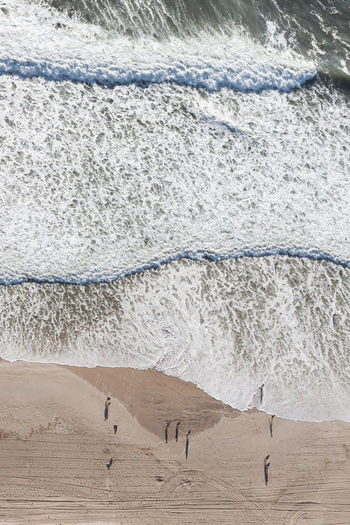 High angle view of people standing at beach by sea