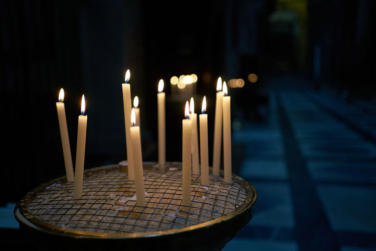 Close-up of illuminated candles on table at night