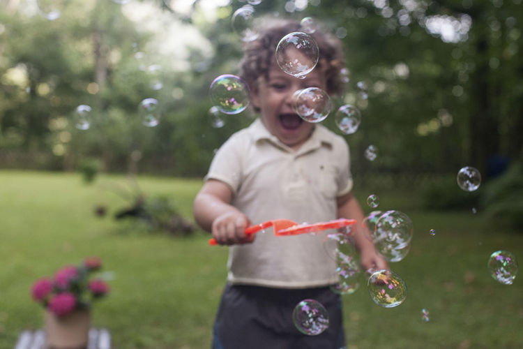 Boy Bubble Bubble Wand Child Childhood Childhood Memories Day Females Focus On Foreground Fragility Front View Innocence Joy Leisure Activity Lifestyles Mid-air Nature One Person Outdoors Plant Real People Smiling Three Quarter Length Vulnerability  Women Moments Of Happiness Exploring Fun