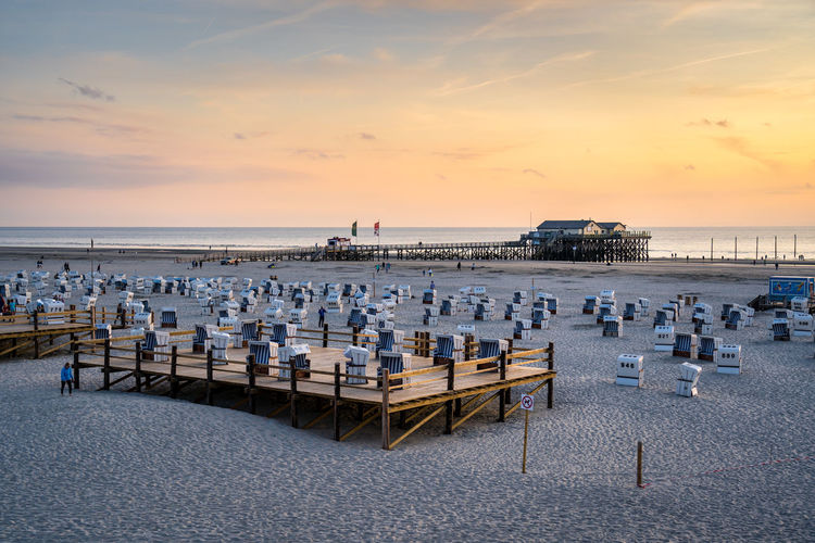 High angle view of chairs on beach against sky during sunset