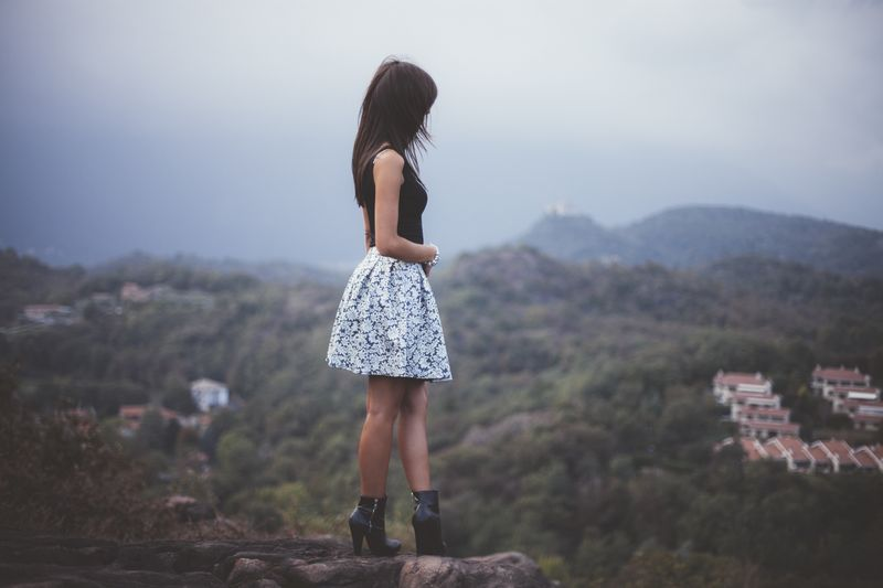 Side view of woman standing on cliff against mountain