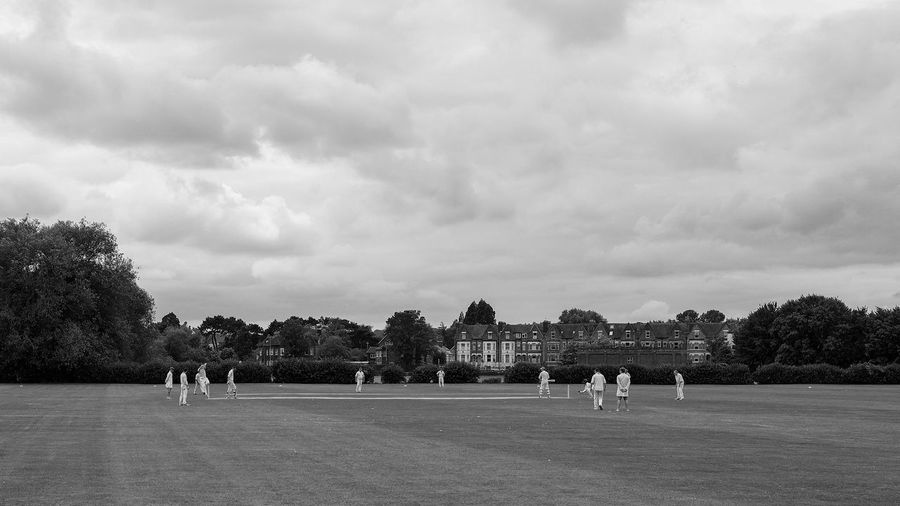 Cricket under a cloud Cricket! Cricket Field Group Of People Tree Sky Plant Cloud - Sky Nature Sport Real People Men People Leisure Activity Day Playground Outdoors Lifestyles Teamwork Playing Park Crowd
