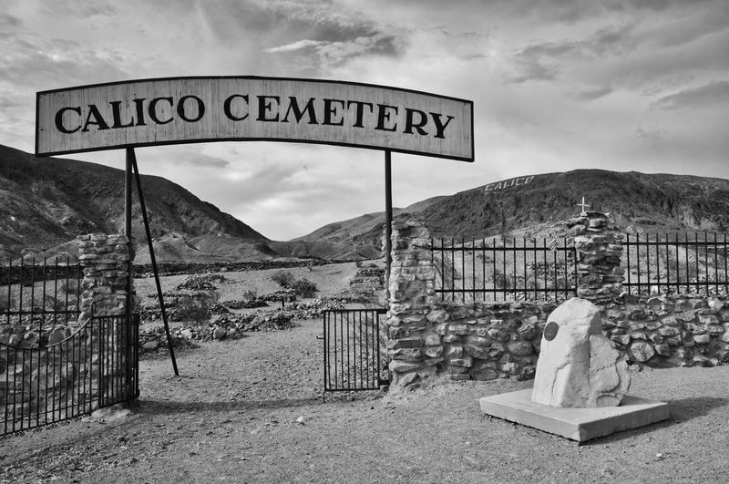 Cemetery sign on landscape against cloudy sky in ghost town in america
