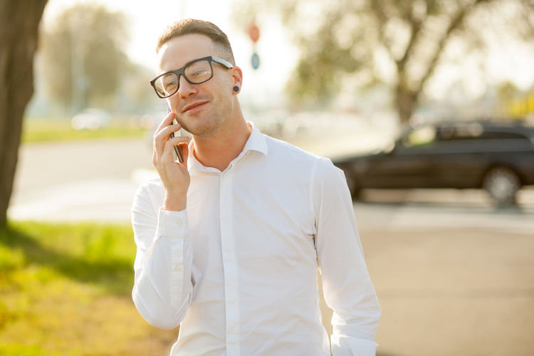 Young man talking on mobile phone while standing in city