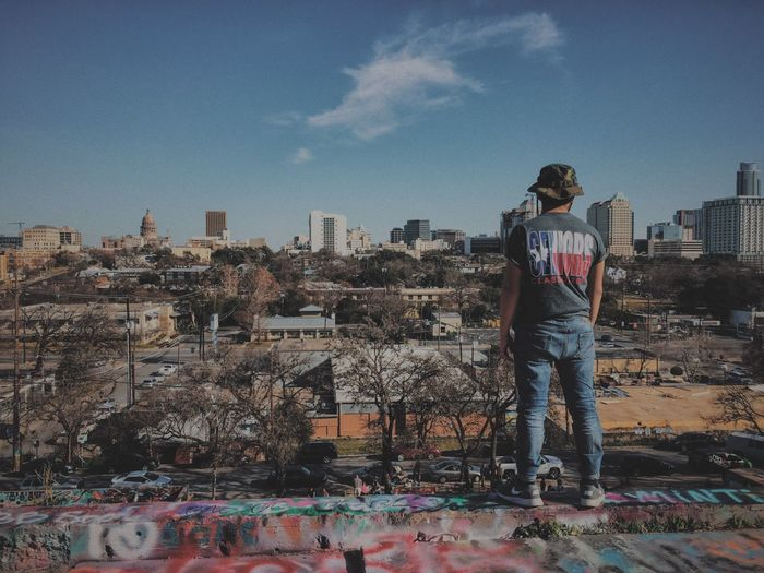 Rear View Of Man Looking At Buildings While Standing On Terrace In City