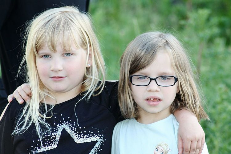 Close-up portrait of siblings with hands on shoulder outdoors