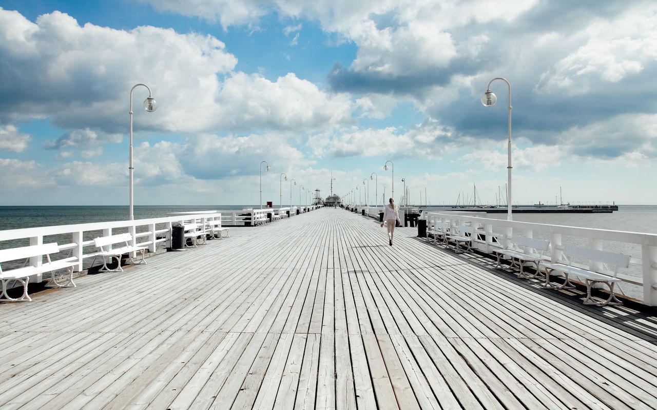 sky, cloud - sky, street light, the way forward, sea, direction, water, nature, day, transportation, pier, lighting equipment, outdoors, diminishing perspective, built structure, no people, empty, street, architecture, horizon over water