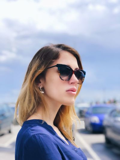 Close-up of beautiful young woman wearing sunglasses against sky