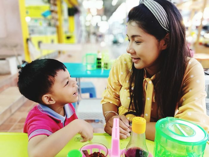 Close-up of smiling mother and son sitting at restaurant