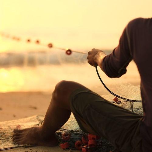 Cropped image of fisherman at sunset