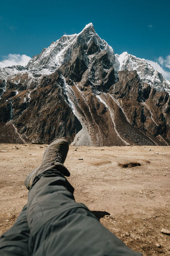 Low section of person on snowcapped mountain against sky