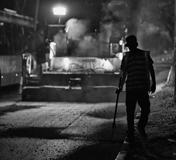 Manual worker with tool walking on roadside at construction site during night