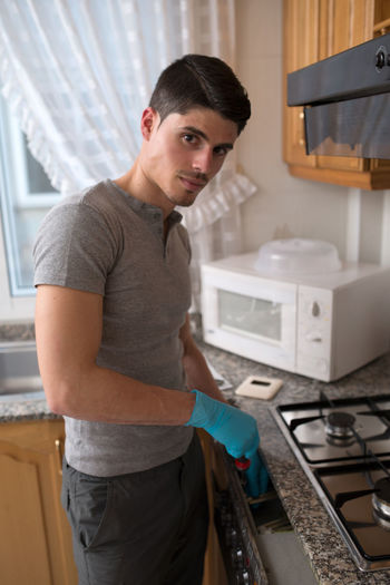 Portrait Of Young Man Repairing Stove In Kitchen