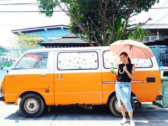 Full length of woman with umbrella standing against van on road
