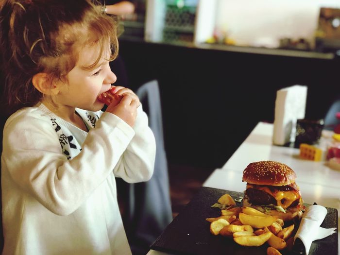Food One Person Real People Food And Drink Indoors  Childhood Table Restaurant Lifestyles Focus On Foreground Women Girls Unhealthy Eating Child Ready-to-eat Looking Fast Food Business Burger Snack
