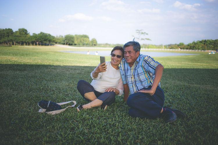 Rear view of friends sitting on grassy field