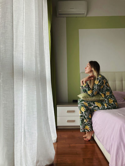 Side view of woman sitting on bed at home