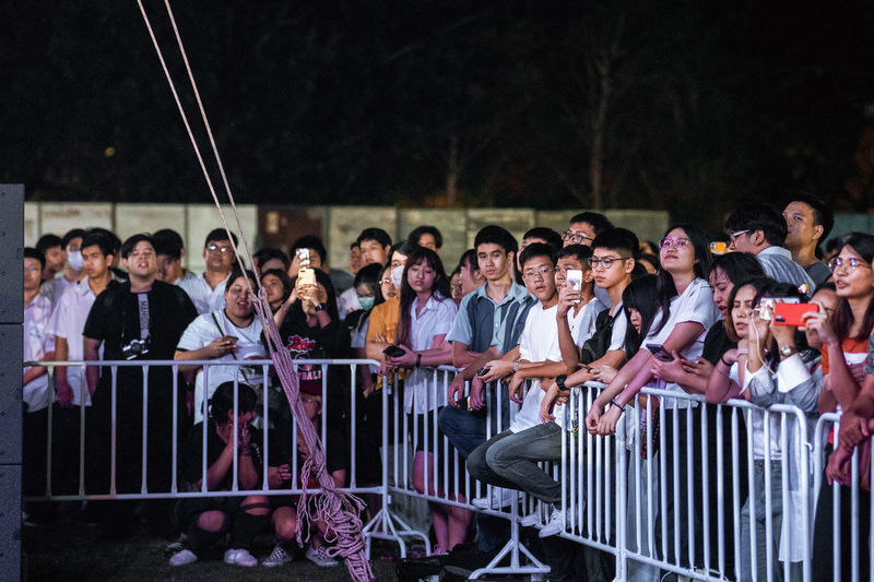 Group of people sitting by railing at night