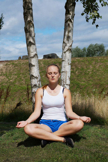 Day Eyes Closed  Fitness Full Length Girl Leisure Activity Lifestyles Lotus Position Meditation Nature Outdoors Park Person Relaxation Shorts Sitting Sport Training Tree Woman Yoga Young Woman