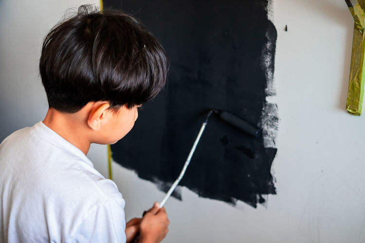 Young child painting a wall in black colour. view from behind.