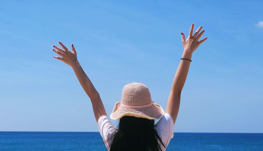 Rear view of woman with arms raised in sea against sky