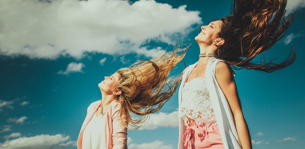 Cheerful young friends tossing hair against sky