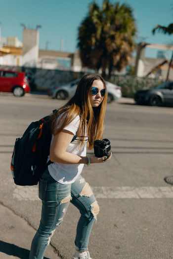 Young woman wearing sunglasses on street in city