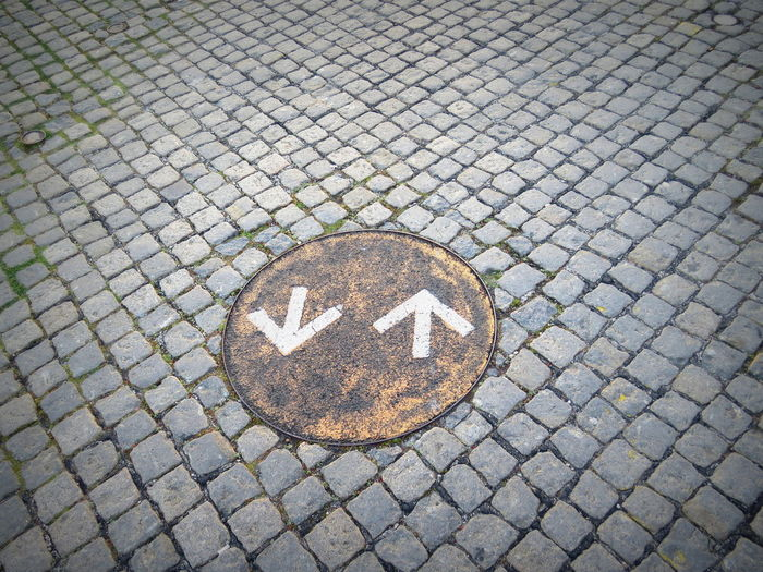High angle view of arrow symbol over manhole lid on footpath