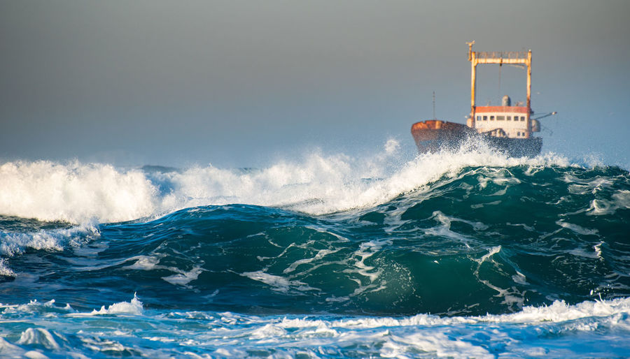 Abandoned ship in the stormy sea with big wind waves during sunset.