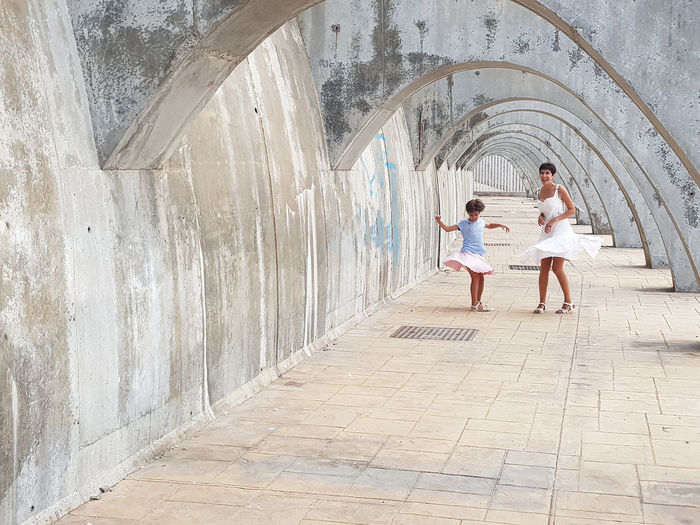 Funny mother and daughter dancing under the arches of the Port of Malaga in Andalusia, Spain. Females wearing dress. Dancing Dress Fun Happiness Mother Adult Arch Architecture Built Structure Casual Clothing Childhood Daughter Day Females Full Length Group Of People Leisure Activity Lifestyles Mid Adult Outdoors People Real People Togetherness Women
