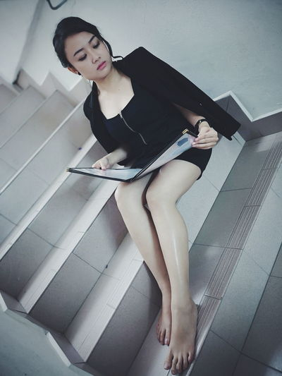 High angle view of woman holding papers while sitting on staircase at home