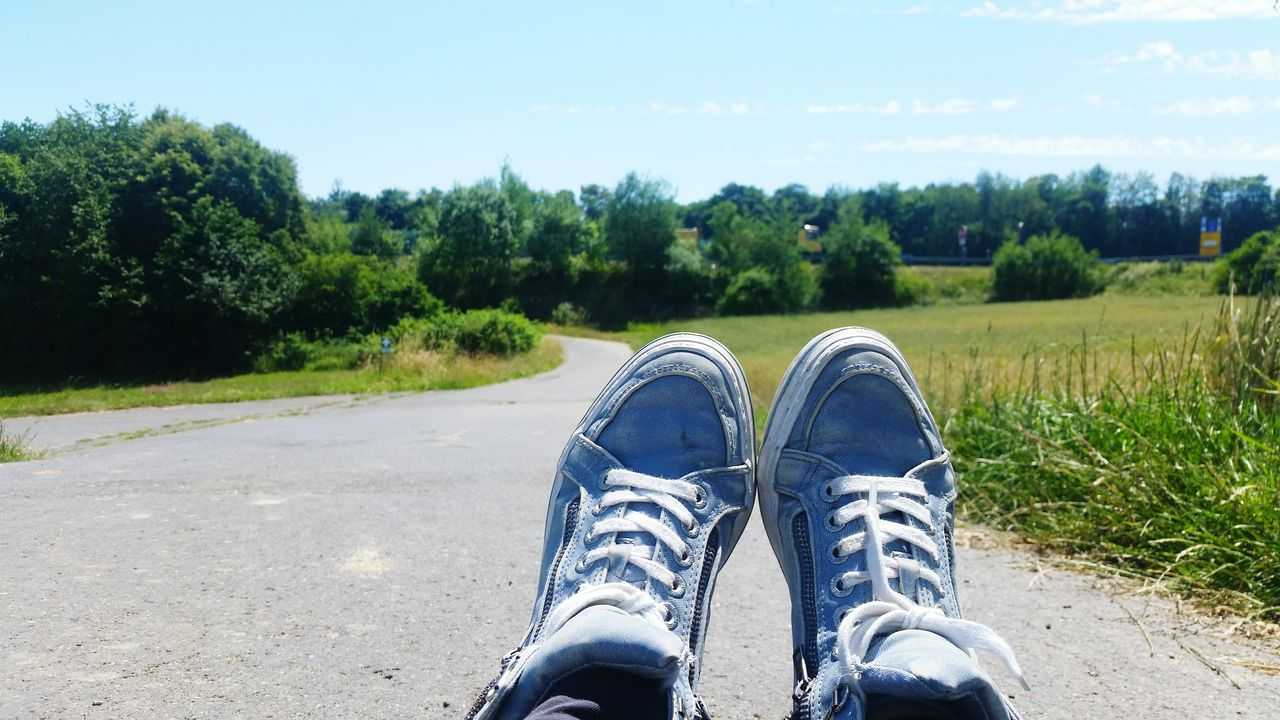 shoe, day, road, tree, one person, outdoors, real people, growth, green color, standing, low section, nature, human body part, grass, sky, beauty in nature, people