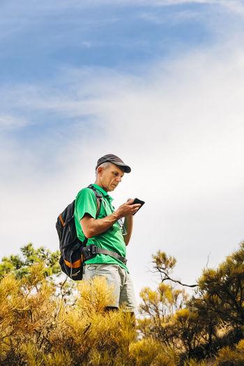 Senior backpacker using smart phone on cliff against sky