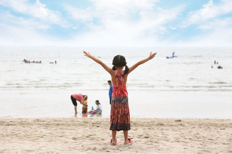 Rear view of woman with arms raised on beach against sky