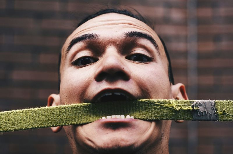 Portrait Of Man Carrying Belt In Mouth Against Wall