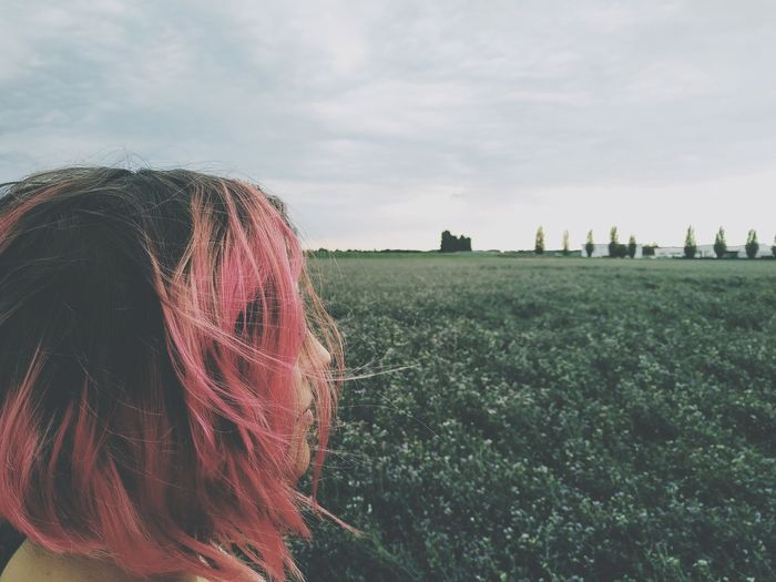 Woman with dyed hair on landscape against sky