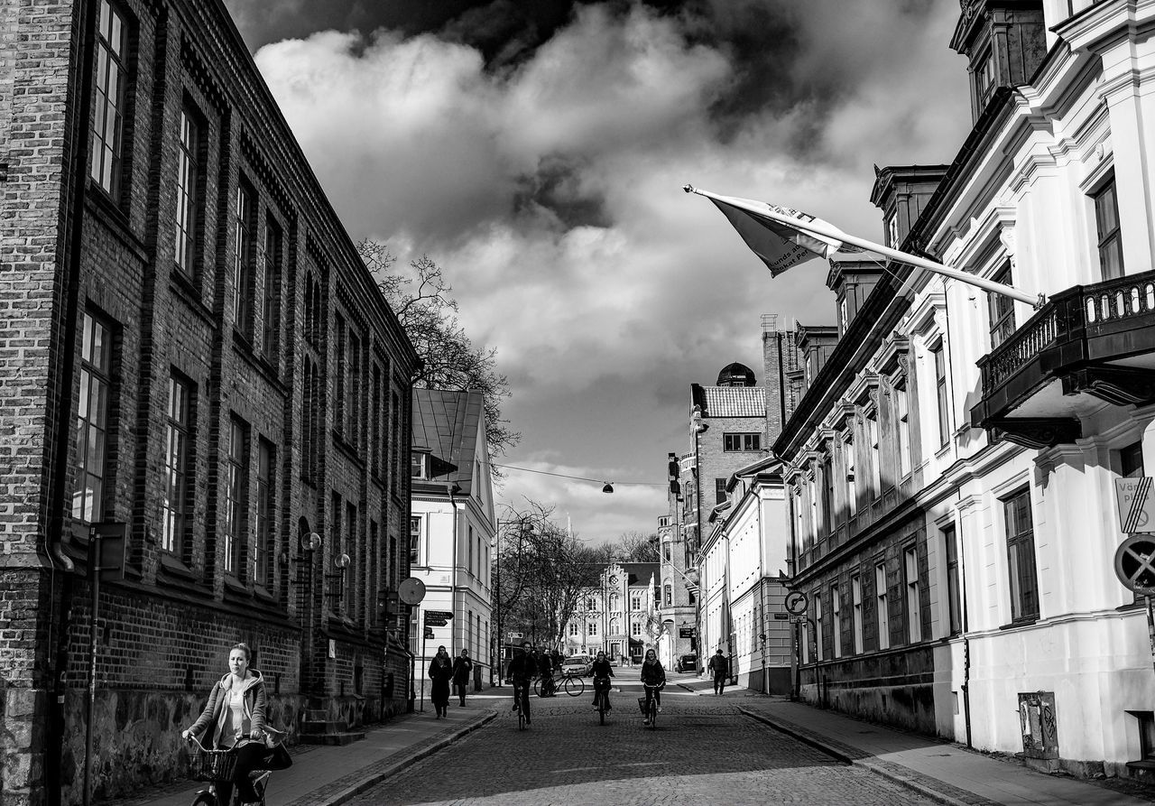 architecture, building exterior, cloud - sky, sky, built structure, real people, street, city, walking, day, outdoors, men, road, women, large group of people, people
