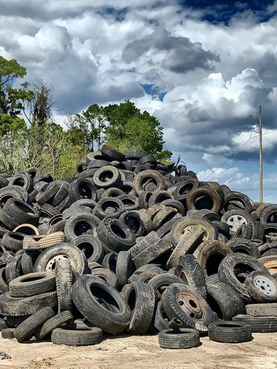 Stack of abandoned vehicle against sky