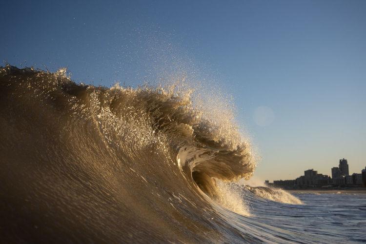 Sea waves splashing against clear blue sky