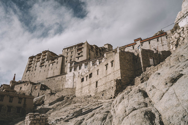 Low angle view of old buildings against cloudy sky