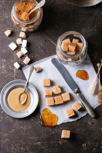 Fudge candy and caramel on baking paper and in glass jar, served over dark background with plate of caramel sauce and sugar cubes. Top view. Baking Paper Beige Brown Butterscotch Candy Caramel Confection Confectionery Creamy Cubes Dark Background Dark Photography Dessert Food Food And Drink Fudge Glass Jar Homemade Food Ingredient Mason Jar Sugar Sweet Food Table Toffee Top View Of Food