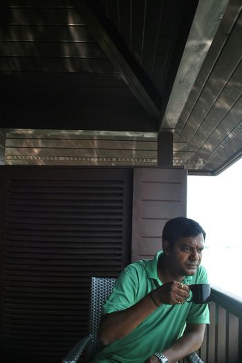 Man having coffee while sitting in porch