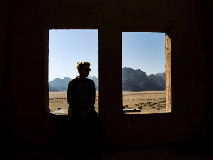 Woman sitting on window against mountains