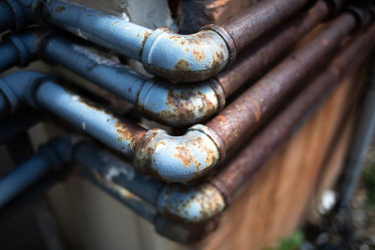 Close-up of rusty pipes mounted on wall
