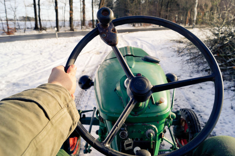 Cropped image of person driving tractor on snow covered road during winter