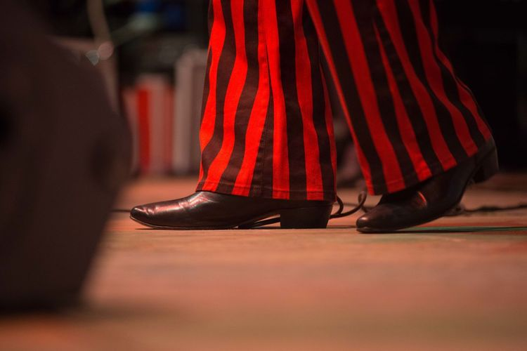 Low section of performer wearing stripped pattern costume on stage
