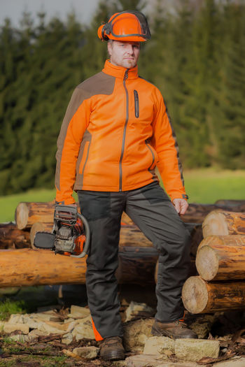 Portrait of lumberjack standing with chainsaw by logs