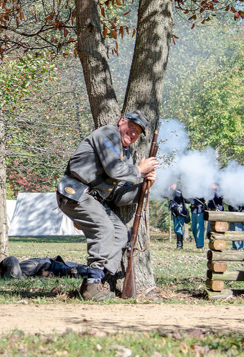 oct 8, 4th Annual Mooresville Civil War Days , South Haven, Michigan; a southern soldier hides behind a tree as he reloads his rifle during a civil war reenactment Acting Actors Camping Civil War Civil War Re-enactments Event Fight Michigan, USA Nature Soldiers USA Uniforms Union Editorial  Guns History Men North Vs South Outdoors People Reenactment Smoke - Physical Structure Tree Weapon Weopons The Photojournalist - 2018 EyeEm Awards