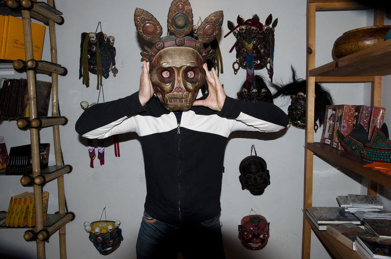 Portrait of man holding mask at home